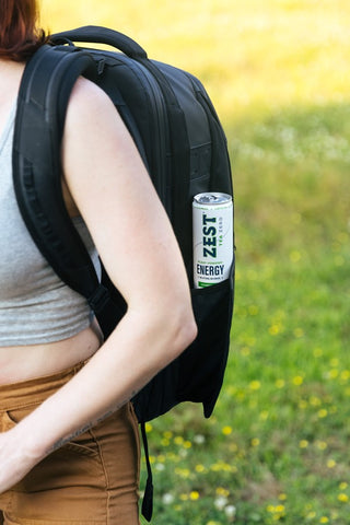 woman hiking with zest sparkling energy tea in her backpack