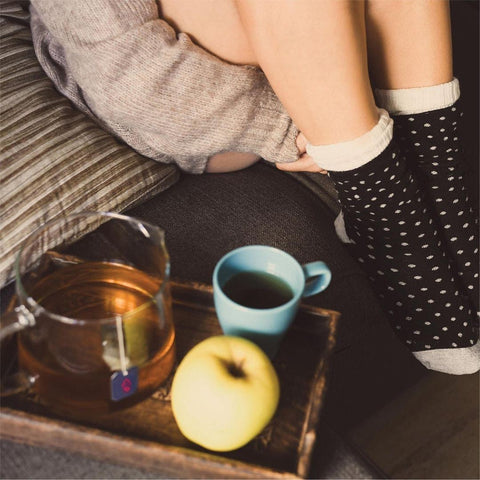 Shot of a girl's legs with black socks, and a tray showing in the foreground with a tea cup, a tea pot containing a Zest tea bag, and an apple.