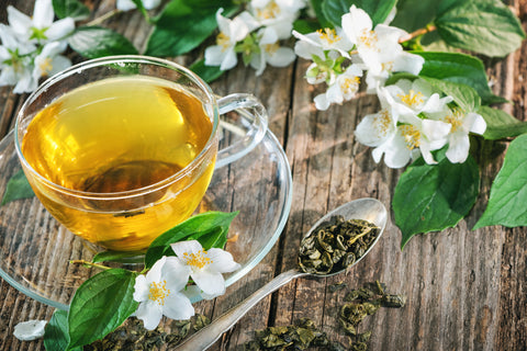 Tea cup with jasmine flowers and loose leaf on a spoon on a wooden table