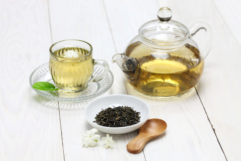 Loose leaf tea with jasmine flowers in front of a tea pot and tea cup