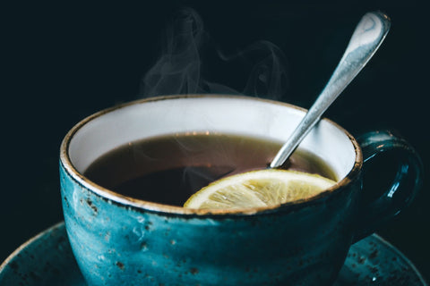 Blue cup filled with tea, a spoon, and a slice of lemon