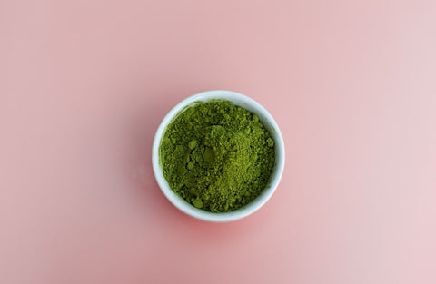 Bowl of matcha tea powder viewed from the top on a light pink background