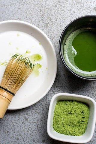 Bowl with matcha, a bamboo whisk, and a cup of matcha powder on a table