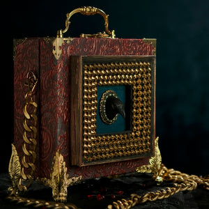 Framed raven head on red and cyan brocade hand bag