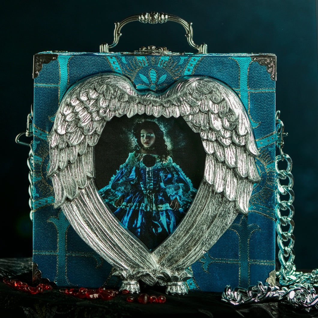 Infanta in a hand carved heart frame hand bag