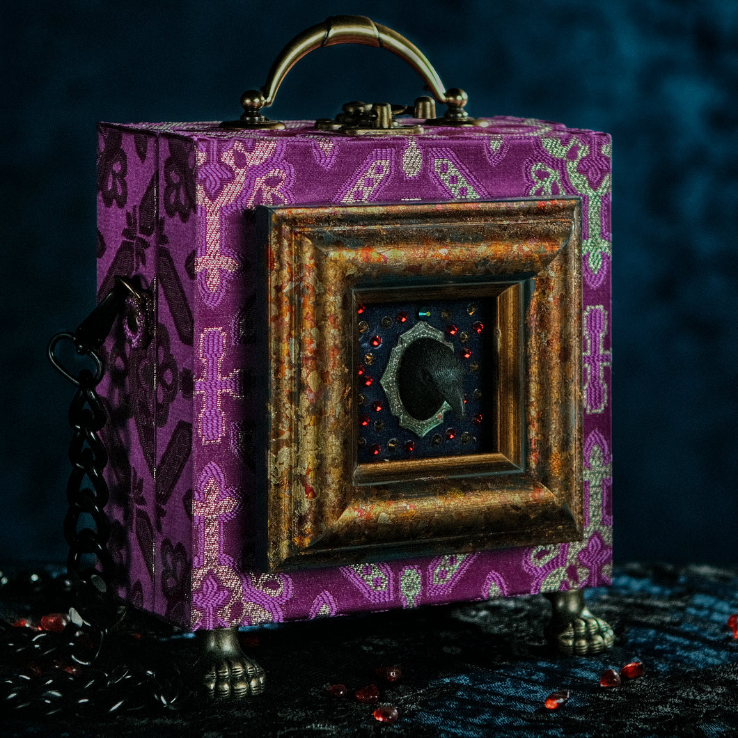 Framed raven head on purple and silver brocade hand bag