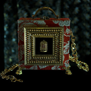 Framed Cage on red brocade hand bag