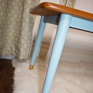 MCM teak coffee table, close up view of the tapered legs professionally refinished in Autentico Bleu Clair paint. Light blue, soft pop of colour.