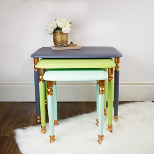 Set of three nest tables, blueish-grey, light lime green, mint, with copper accents.
