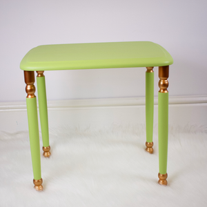 Medium table from set of 3. Light lime green with copper accents on the top and bottom of legs.