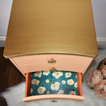 Vintage bedside table with gold painted top and peach drawers