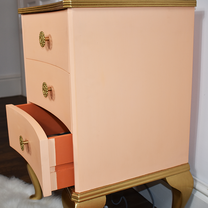 Side view peach bedside drawers with gold Queen Anne legs and top.