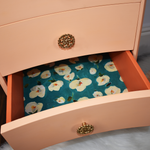 Peach bedside drawers lined with teal and white floral paper, vintage professionally refinished