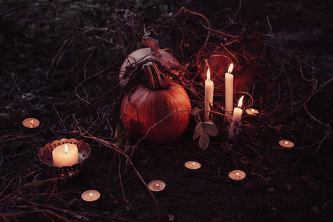 Haunted Pumpkin surrounded by roots, plants and candles