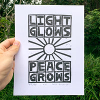 "Block printed poster by artist Louis Bicycle. Sun. Text ""Light, Glows, Peace, Glows."""