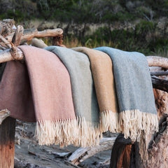 Four pastel coloured blankets are lined up on a piece of driftwood