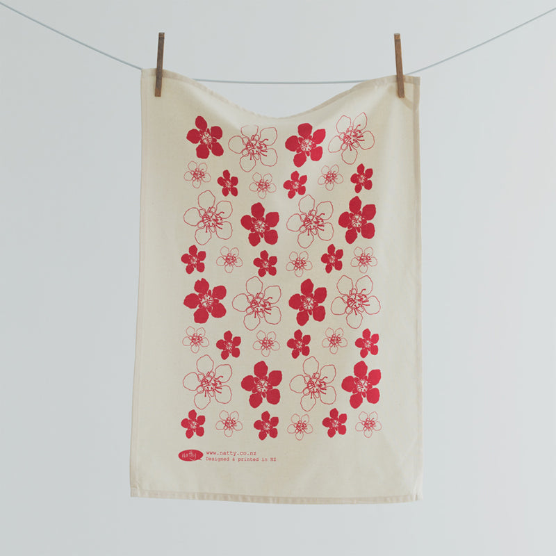 A tea towel featuring red flowers native to NZ