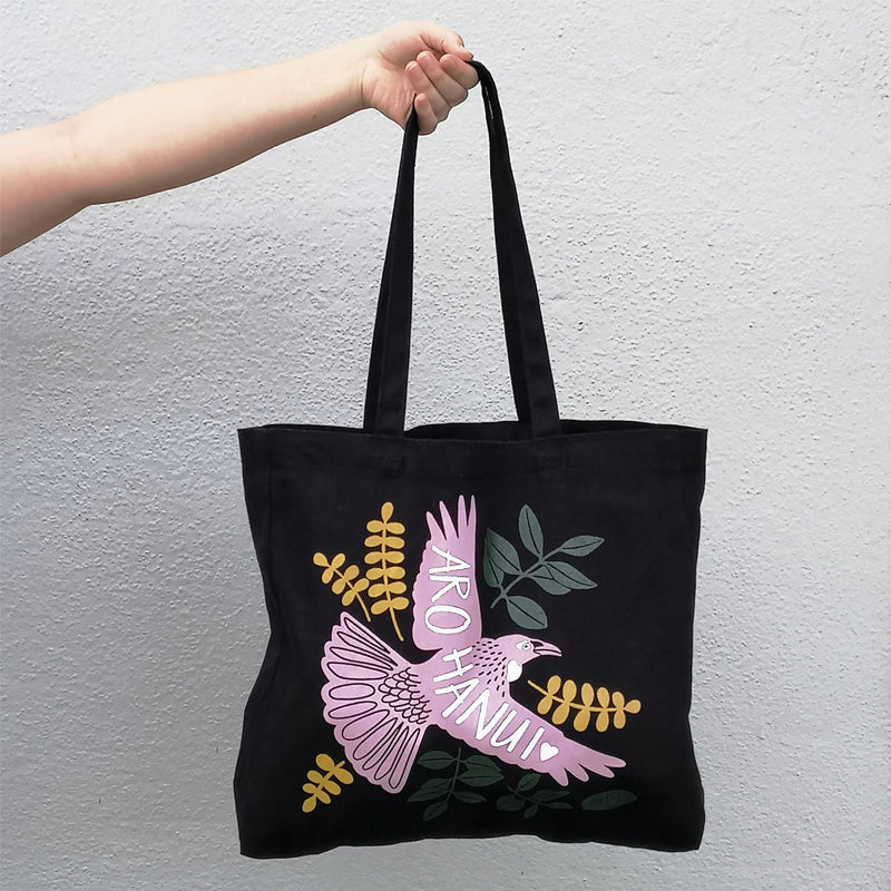 An arm holdinga canvas tote bag featuring a tui and the phrase Arohanui