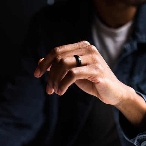 man holding hand with a black tungsten ring on it