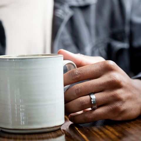 man holding coffee cup with ring on his hand