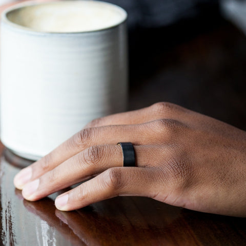 coffee cup with a man's hand next to it with a wedding ring