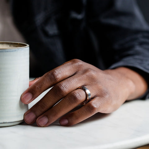 mans hand next to coffee cup on table with ring