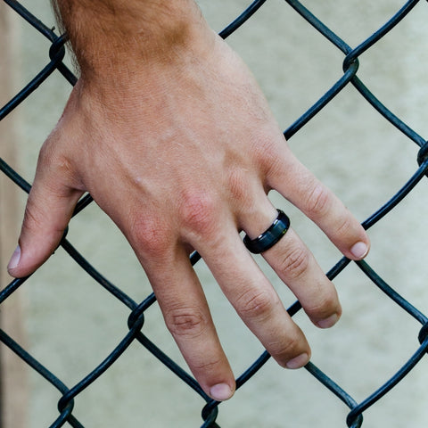 mans hand on a fence with wedding band on