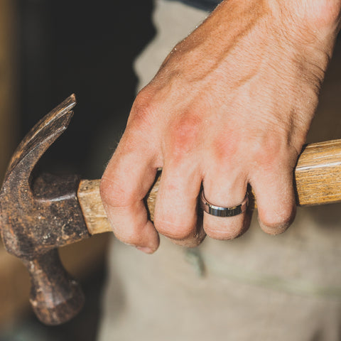 man holding hammer with tungsten ring