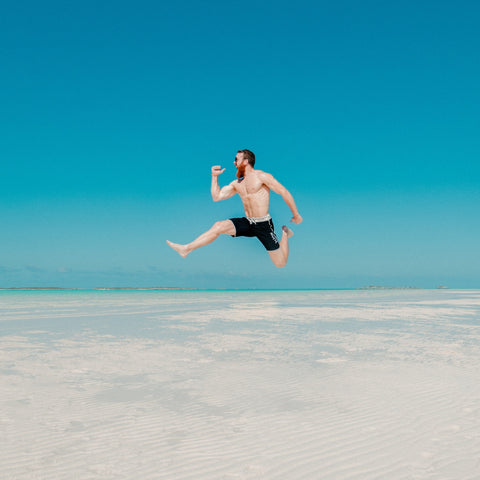 man on beach jumping in water