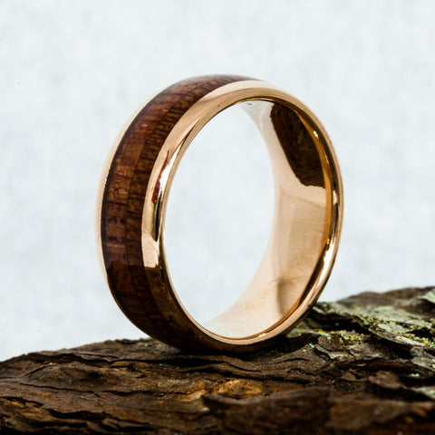 wood inlay tungsten ring laying on a rock