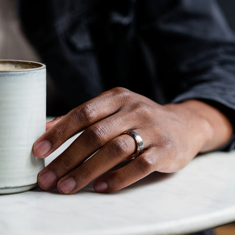 man with wedding ring holding coffee cup