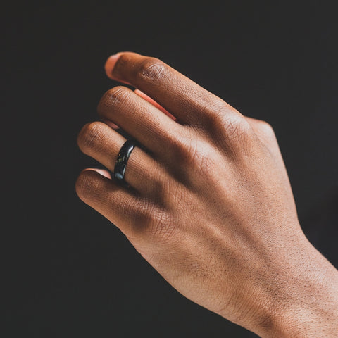 mans hand with black wedding band