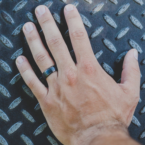 mens hand with wedding band on background