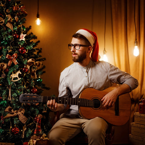 man holding guitar with glasses in a santa hat