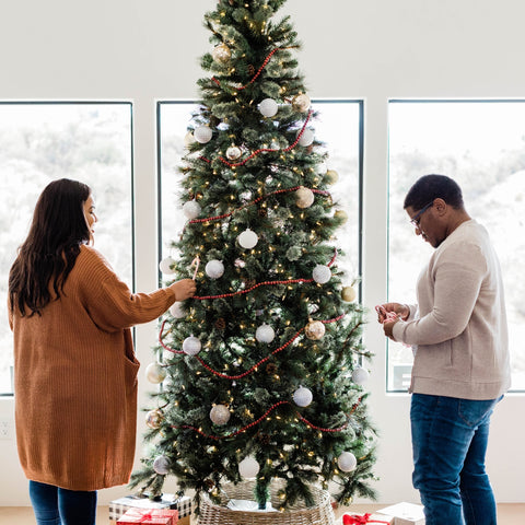 couple decorating a Christmas tree