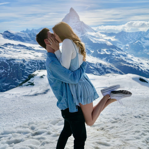 couple kissing on top of mountain in the snow