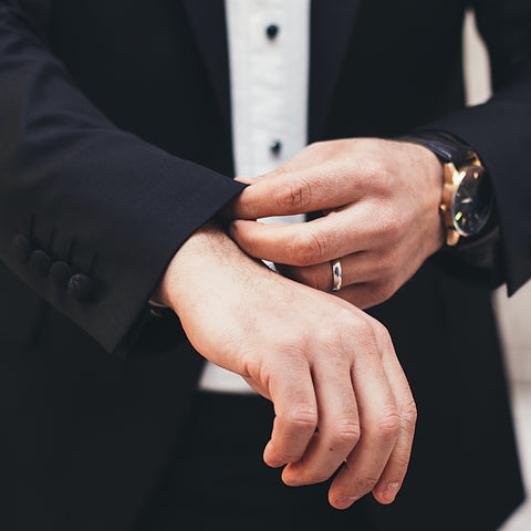 groom checking his sleeve with watch and a ring on his hand