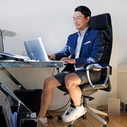 man sitting at desk with slippers and a blazer