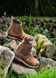 Image of a pair of buckler safety dealer boot in dark brown leather in rocky terrain