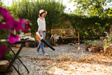 A woman using the BGA 45 Cordless blower to clear away leaves and debris in a garden. A broom in the background indicates how easy to blower is to use in comparison