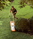 STIHL RMA 235 Walk Behind / Push Mower in orange with white details being used by a man in his garden