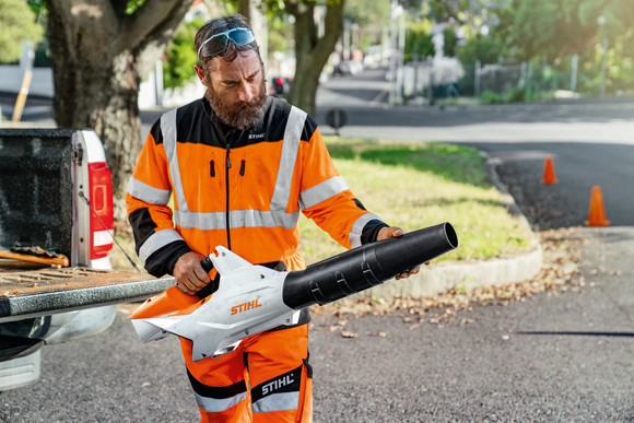 Image shows a man dressed in STIHL overalls holding the STIHL BGA 86 Cordless Blower