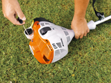 A close up image of someone starting up the STIHL FS 40 Strimmer on the ground