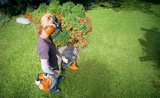 A woman using the FS 40 Petrol Strimmer to trim grass around a large rock in a garden. She is wearing appropriate safety gear including a visor, ear defenders and gloves.