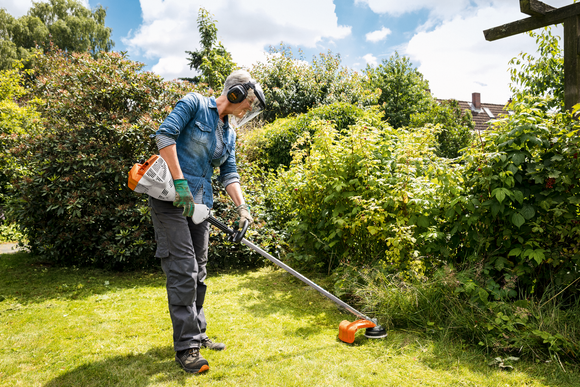 STIHL FS 56 C-E Strimmer being used by a lady wearing protective ear defenders, gloves and a visor. She is strimming the edge of her garden