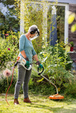 Image shows a lady using the STIHL FSE 60 Brush Cutter to trim the edges of her garden. She wears a safety visor, gloves, and ear protectors