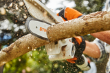 Image shows the STIHL GTA 28 hand held pruner being used to cut a piece of wood