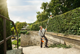 Images shows a man, using safety goggles and the hedge trimmer's safety harness, using the STIHL HLA 85 Battery powered hedge trimmer to trim the top of a tall hedge. Using the angled head capability