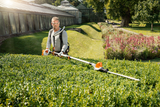 Image shows a man, wearing safety goggles and using the STIHL HLA 85 Hedge Trimmer backpack, using the battery powered hedge trimmer to trim the top of a lower hedge using the angled head capability.