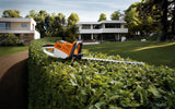 Image of a garden with white houses in the background, showing the STIHL HSA 66 Hedge Trimmer resting on the top of a hedge